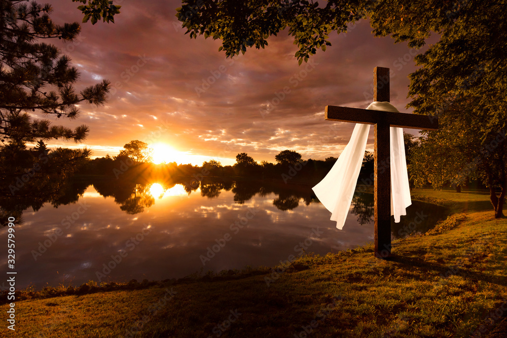 Fototapeta Beautiful photo illustration of an Easter morning sunrise on a cross by a calm lake. The warm light almost announces Jesus's rising from the dead.