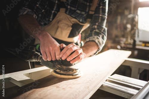Close up of sanding a wood with orbital sander at workshop Fotobehang