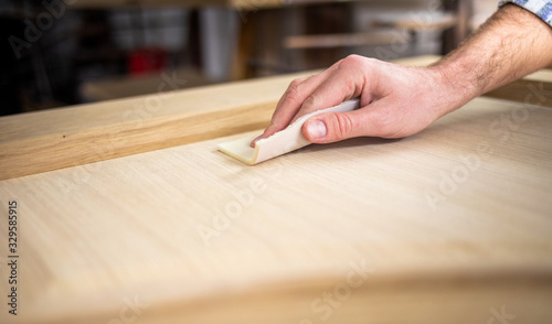 Photo Close up of abrasive paper polishing a wooden board