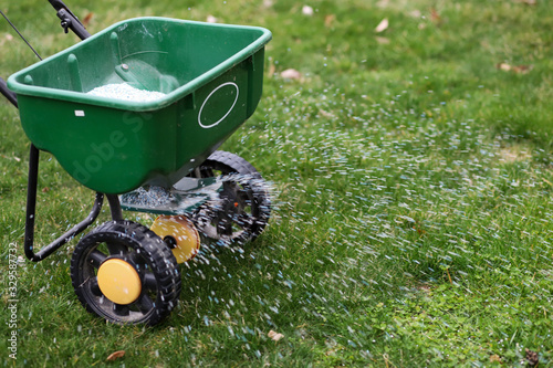 Fototapeta A  seed  and  fertilizer spreader sitting  out on a lawn obraz