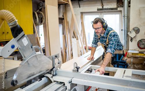 Carpenter using circular saw to cut a large wooden board at carpentry workshop Wallpaper Mural
