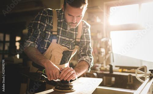 Foto Carpenter at workshop polishes wooden board with a electric orbital sander