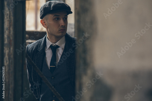 Canvastavla A man posing in the image of an English retro gangster dressed in a coat, suit and flat cap