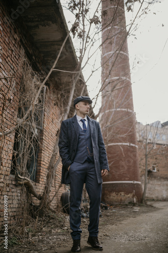Photo A man posing in the image of an English retro gangster dressed in Peaky blinders style near abandoned building