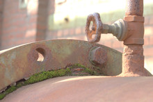 A Large Rusted Pipe Covered With Moss And A Shut-off Valve