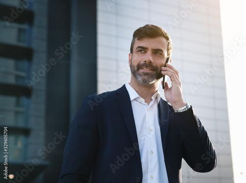 Empresario hablando por teléfono en distrito financiero Wallpaper Mural