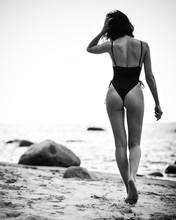 Beautiful Lady In Black Swimsuit Walks On A Sandy Beach