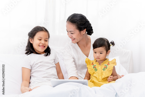 Photo Mother and two daughters enjoy watching cartoon from tablet