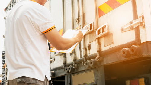 Canvastavla Truck driver holding clipboard inspecting safety a truck door