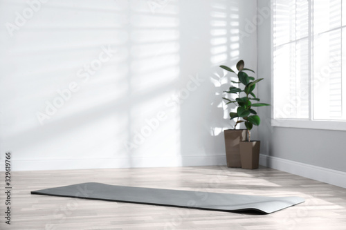 Obraz Unrolled grey yoga mat on floor in room - fototapety do salonu