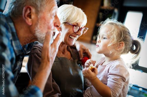 Obraz Happy grandparents with grandchildren making breakfast in kitchen - fototapety do salonu