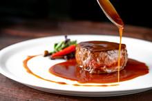 Grilled Beef Tenderloin Steak On A White Platter Is Served With Demiglas Sauce