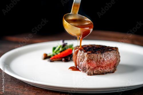 Fototapeta Grilled beef tenderloin steak on a white platter is served with demiglas sauce obraz