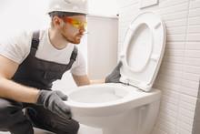 Plumber Installing Toilet Bowl...