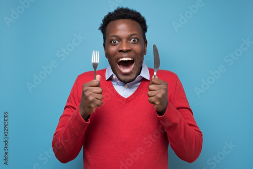 Fototapeta Young hungry african man holding a fork and a knife waiting for delicious meal