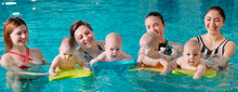 A Group Of Mothers With Their Young Children In A Children's Swimming Class With A Coach.