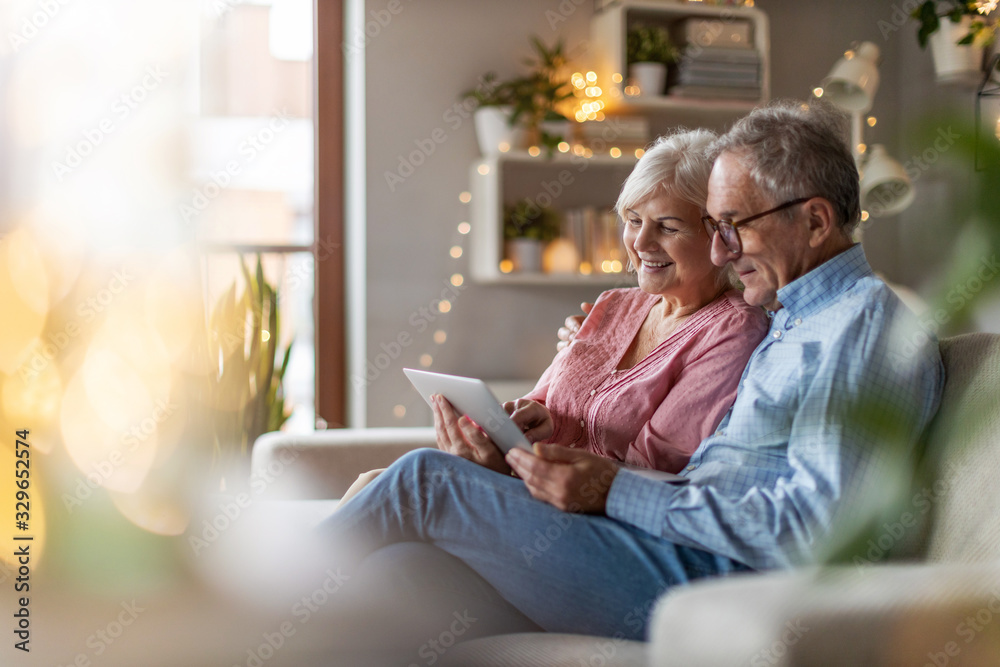 Fototapeta Mature couple using a laptop while relaxing at home