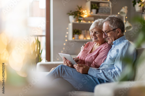 Mature couple using a laptop while relaxing at home Canvas Print