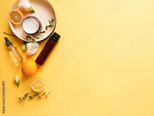 Fototapeta flatlay composition with cream, lotion, oil, flower, citrus and eucalyptus on yellow background. Concept beauty natural vitamin cosmetic product, skin care, copyspace, top view obraz