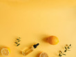bright flatlay composition with oil, citrus and eucalyptus. on yellow background. Concept beauty natural vitamin cosmetic product, skin care, copyspace, top view