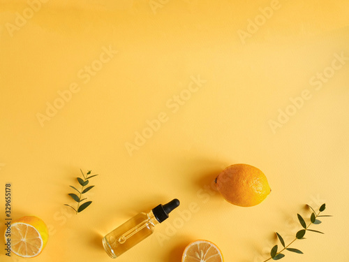 Obraz bright flatlay composition with oil, citrus and eucalyptus. on yellow background. Concept beauty natural vitamin cosmetic product, skin care, copyspace, top view - fototapety do salonu