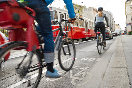 Dangerous encounter between cyclists, cars and tram at the end of a marked bike path on busy road with lots of traffic in Vienna Canvas Print