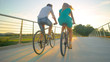 LOW ANGLE: Unrecognizable couple riding their bikes across an overpass at sunset