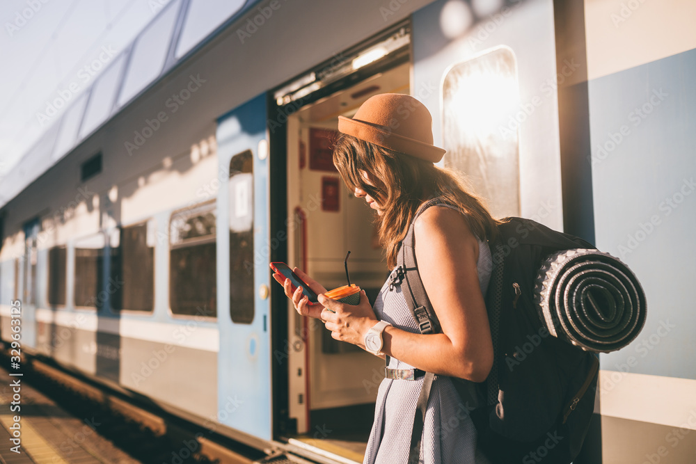 Fototapeta Railroad theme. Beautiful young woman with a backpack uses the phone while standing near the railroad train on the platform. Cheap travel