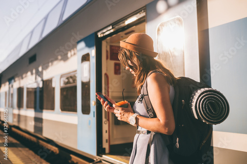 Fototapeta Railroad theme. Beautiful young woman with a backpack uses the phone while standing near the railroad train on the platform. Cheap travel obraz