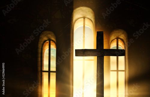 Fototapeta Wooden cross wrapped in light that filters through the windows inside a church