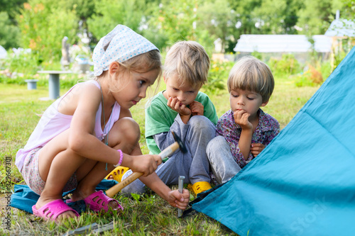 Obraz cute little boys and girl toddlers help set up a camping tent. family with little children have fun spending summer holidays in nature outdoor - fototapety do salonu