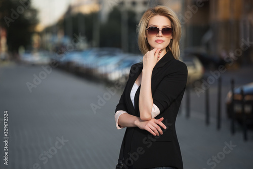 Fototapeta Young fashion blond business woman in black blazer and sunglasses obraz