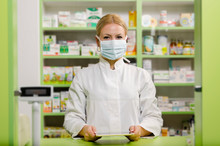 Pleasant Professional Young Female Pharmacist With Surgical Mask Smiling
