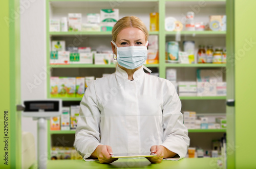 Fotografia Pleasant professional young female pharmacist with surgical mask smiling