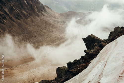 Photo Beautiful pointy cliff on high rocky mountain edge with snow among thick low clouds