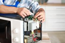 Worker Repairing Microwave Ove...