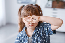 Little Girl With Word NO On Her Palm At Home. Concept Of Violence