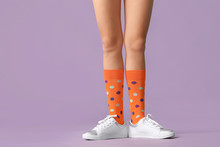 Legs Of Young Woman In Socks And Shoes On Color Background