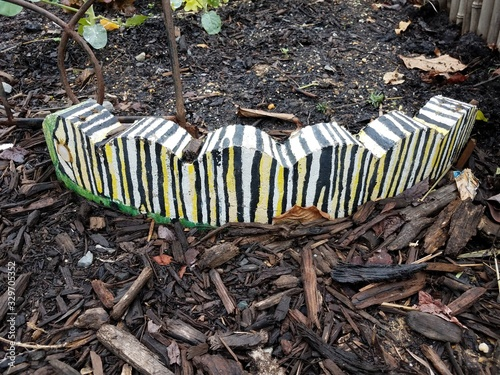 yellow and black and white stone caterpillar with mulch in garden