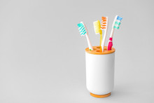 Holder With Tooth Brushes On Light Background
