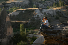 Man Sitting On Cliff And Looks...