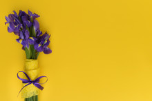 Bouquet Of Beautiful Spring Irises On A Yellow Background. Flowers Are Decorated With Yellow And Purple Ribbon. Greeting Card For Women's Day, Mother's Day, Easter. Floral Mood. Copy Space.