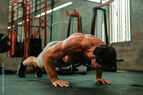Fototapeta Handsome Man exercise in gym body-building with muscular strong body