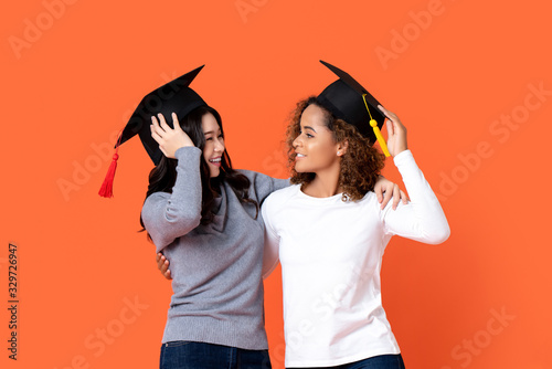 Portrait of two happy mixed-race women graduating holding there graduation caps Wallpaper Mural