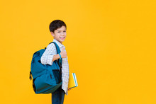 Smiling Handsome Mixed Race Schoolboy With Books And Backpack Giving Thumbs Up Isolated On Yellow Background With Copy Space
