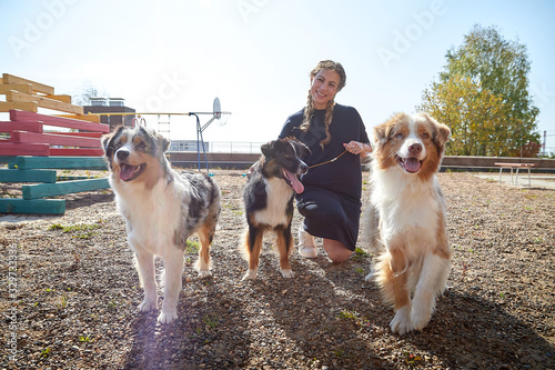 Fényképezés Pretty funny girl with nice dog at children playground in the yard of city in a