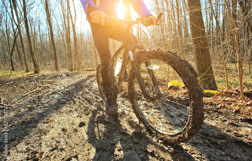 The cyclist is riding on mountain bike on dirt trail in forest in the early spri Wallpaper Mural