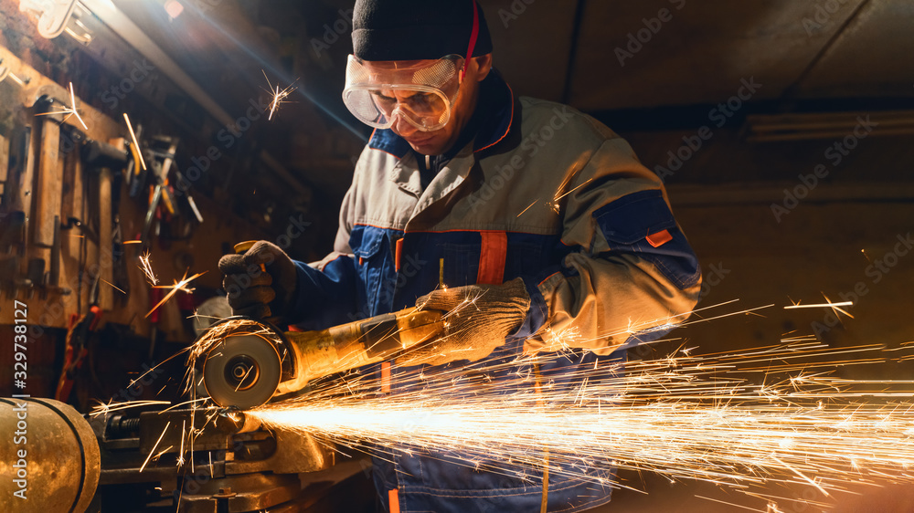Fototapeta Locksmith in special clothes and goggles works in production. Metal processing with angle grinder. Sparks in metalworking