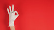 canvas print picture - A Okay hand sign with gloves in left hand on red background.