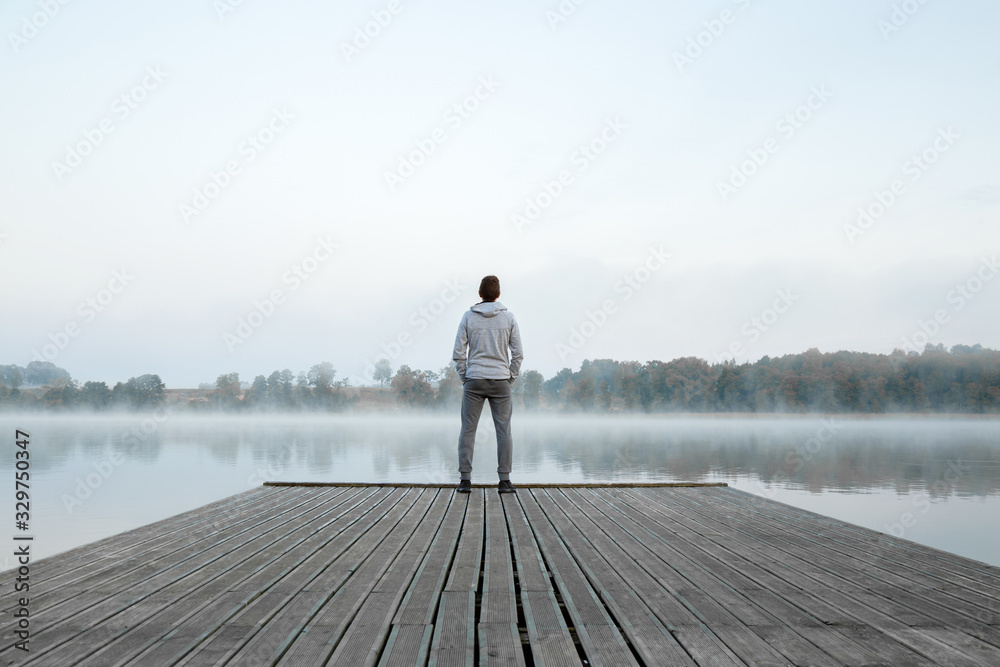 Fototapeta Young man standing alone on wooden footbridge and staring at lake. Thinking about life. Mist over water. Foggy air. Early chilly morning. Peaceful atmosphere in nature. Enjoying fresh air. Back view.